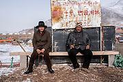 Zado, Tibet (Qinghai, China). Men sit on a bench overlooking the Mekong river.
