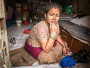 02 AUGUST 2015 - BHAKTAPUR, NEPAL:  A woman sits in her temporary shelter in Bhaktapur. The Nepal Earthquake on April 25, 2015, (also known as the Gorkha earthquake) killed more than 9,000 people and injured more than 23,000. It had a magnitude of 7.8. The epicenter was east of the district of Lamjung, and its hypocenter was at a depth of approximately 15 km (9.3 mi). It was the worst natural disaster to strike Nepal since the 1934 Nepal–Bihar earthquake. The earthquake triggered an avalanche on Mount Everest, killing at least 19. The earthquake also set off an avalanche in the Langtang valley, where 250 people were reported missing. Hundreds of thousands of people were made homeless with entire villages flattened across many districts of the country. Centuries-old buildings were destroyed at UNESCO World Heritage sites in the Kathmandu Valley, including some at the Kathmandu Durbar Square, the Patan Durbar Squar, the Bhaktapur Durbar Square, the Changu Narayan Temple and the Swayambhunath Stupa. Geophysicists and other experts had warned for decades that Nepal was vulnerable to a deadly earthquake, particularly because of its geology, urbanization, and architecture.      PHOTO BY JACK KURTZ