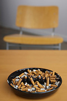 Full ashtray of cigarettes on table