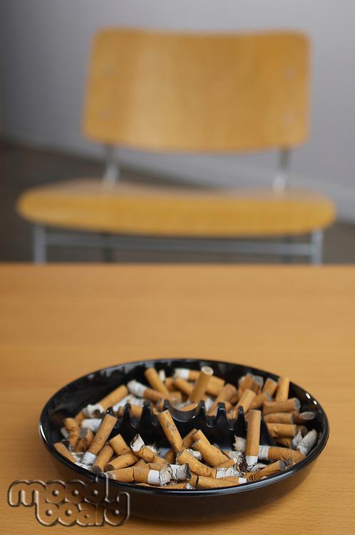 Full ashtray of cigarettes on table