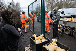 Harefield, UK. 13 January, 2020. Stop HS2 activists observe a team of construction engineers erecting a gate across a public right of way leading to an activist protection camp. Activists were evicted by bailiffs from part of the nearby Colne Valley protection camp last week. 108 ancient woodlands are set to be destroyed by the high-speed rail link and further destruction of trees for HS2 in the Harvil Road area is believed to be imminent.