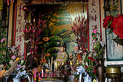 Buddha statues are on display inside a bright and colorful Buddhist temple in Chiang Rai, Thailand.