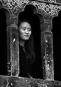 A woman looks out of her home in rural Bhutan.