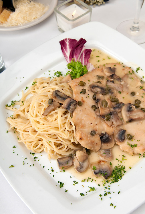 Plate of chicken picatta, lightly dredged in flour, sauteed in lemon, butter and white wine with fresh mushrooms and spaghetti pasta.