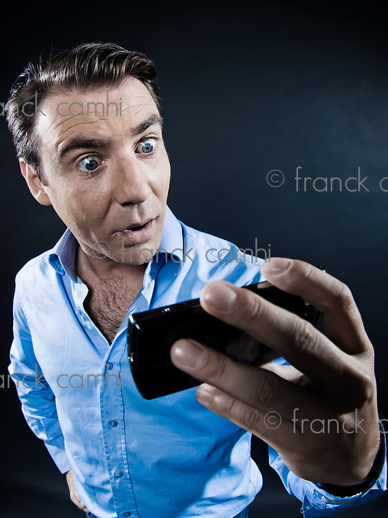 caucasian man looking at cellphone surprised portrait isolated studio on black background