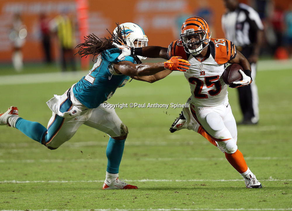 Cincinnati Bengals running back Gio Bernard (25) straight arms Miami Dolphins outside linebacker Philip Wheeler (52) after catching a flat pass for a third quarter gain of six yards during the NFL week 9 football game against the Miami Dolphins on Thursday, Oct. 31, 2013 in Miami Gardens, Fla.. The Dolphins won the game 22-20 in overtime. ©Paul Anthony Spinelli