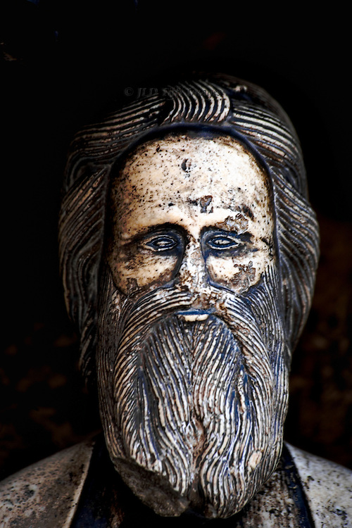Detail, head of St. James, from the statue on the portal, right side.  Hair schematized in narrow incised parallel ridges; stern facial expression.