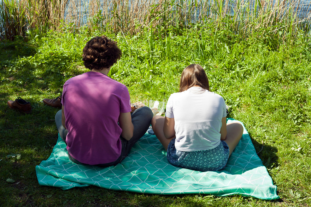 two young people sitting by the water picnicking Netherlands