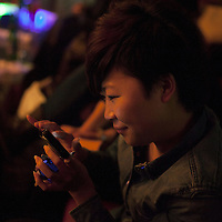 BEIJING, NOVEMBER -24 : a woman in an underground lesbian club in Beijing checks her mobile phone.
