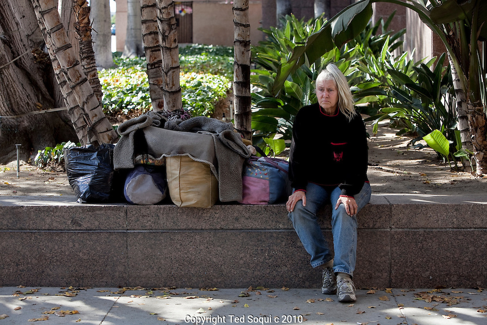 Homeless woman with her belongings in bags sitting outside the L.A. Superior Courthouse where she lives..Downtown L.A. has the largest concentration of homeless people in the U.S.
