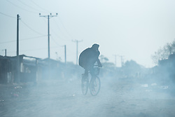 27 January 2019, Micha kebele, Seweyna woreda, Bale Zone, Oromia, Ethiopia: A man rides a bike in Micha. Dust and smoke fills the air, as night fires are dying out, lit by people who sleep on the streets.
