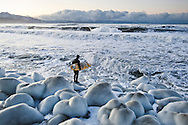 Jake Beaudoin heading out for a winter surf in Alaska.