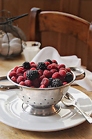 Berries on colander with cream, kitchen background