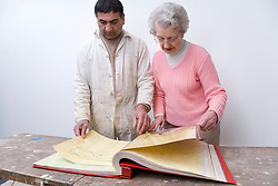 Decorator going through a book of wall paper samples with his client,
