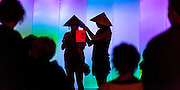 Two Asian girls wearing coolie hats hold a red lantern while standing in front of a colourful illuminated wall.