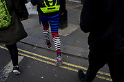 A woman's legs in striped leggings walk across the kerb of a central London street, on 28th March, 2017, in London, England.