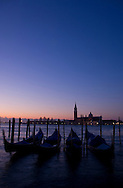 Gondolas at sunrise and San Giorgio Maggiore in silhouette in the background;<br /> Venice, Italy