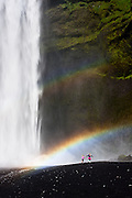 Two little girls hop and skip under the rainbow cause by afternoon light hitting the water spray of Skografoss waterfall