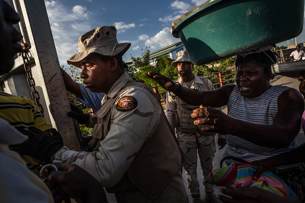 DAJABÓN, DOMINICAN REPUBLIC - JUNE 26, 2015: Haitian women plead for border guards to let them through to go back to Haiti as guards work to shut down the border by closing the gate that separates Haiti and the Dominican Republic. PHOTO: Meridith Kohut for The New York Times