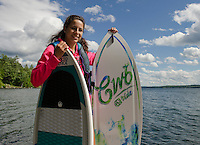 Claudia Cantin grabs a couple of boards and is ready to surf as she heads out on Lake Winnisquam with her family for an evening of wake surfing.  (Karen Bobotas/for the Laconia Daily Sun)