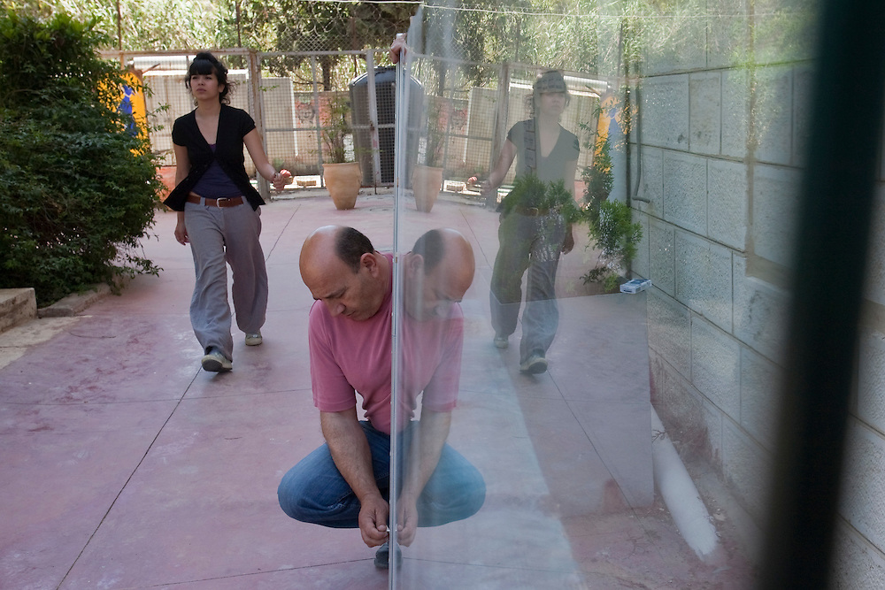 A student walk past a worker fixing a heavy glass door that will displayed at the entrance of the room where will be hang the Picasso paint at the National Academy of art of Palestine in Ramallah on June 06, 2011. Photo by Olivier Fitoussi