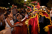 A costumed reveler called a vejigante greets children during the final night of parades during the Carnaval de Ponce February 21, 2009 in Ponce, Puerto Rico. Vejigantes are a folkloric character representing the devil.