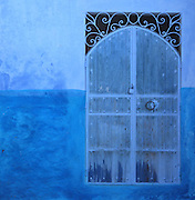 A wooden window shutter with round metal handle and wrought iron work above, painted blue, in the medina or old town of Chefchaouen in the Rif mountains of North West Morocco. Chefchaouen was founded in 1471 by Moulay Ali Ben Moussa Ben Rashid El Alami to house the muslims expelled from Andalusia. It is famous for its blue painted houses, originated by the Jewish community, and is listed by UNESCO under the Intangible Cultural Heritage of Humanity. Picture by Manuel Cohen