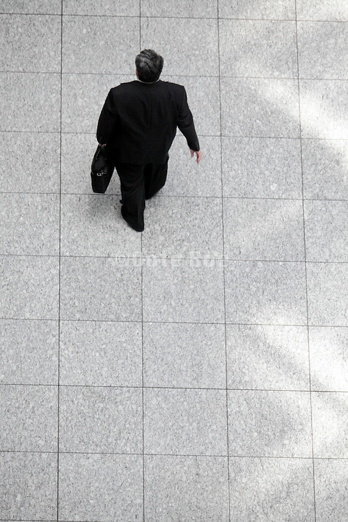 overhead view of businessman walking with light from roof pattern on the floor