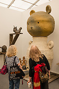 New York, NY - May 3, 2019. Two women seem overwhelmed by ceramic sculptures in the Tokyo's Kaikai KiKi Gallery at the Frieze Art Fair on New York City's Randalls Island.