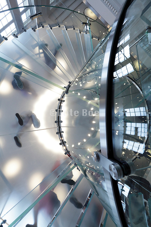 winding glass stair from under with people walking up and down Apple Store Amsterdam