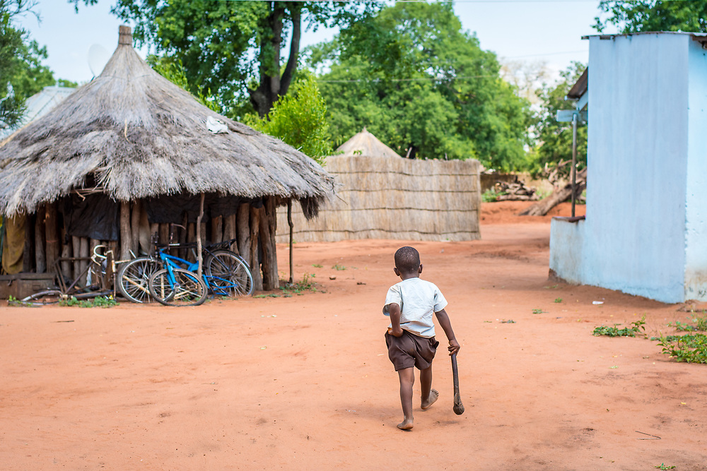 Young Zambian boy walks away through village while holding onto hatchet and his pants, Mukuni Village, Zambia