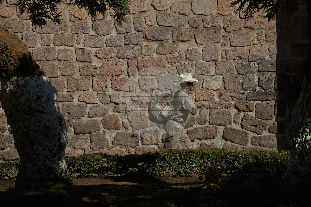 A gardner walks past a stone wall at the Biblioteca Publica or Public Library, a Baroque style building in Morelia, Michoacan state Mexico. The city is a UNESCO World Heritage Site and hosts on of the best preserved collection of Spanish Colonial architecture in the world. The building, constructed in the seventeenth century was originally the temple of Jesus and became a library in 1930.