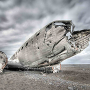 Once a symbol of the golden age of air travel, a Douglas Super DC-3 airplane lies hollow and forgotten on a deserted black beach in Iceland - untouched since it crashed more than four decades ago.<br /> The United States Navy cargo plane is now no more than a husk - dented and bruised by 41 punishing years of Arctic gales and rain.<br /> <br /> Its tail and wings are gone and its windows are all smashed in since it was forced to crash land on S&oacute;lheimasandur beach on Saturday November 24 1973.<br /> <br /> Amazingly, the crew all survived the impact, but the plane was abandoned rather than recovered, meaning the weather-beaten remains are still standing at the crash site.