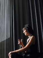 Woman holding champagne in front of curtains indoors side view
