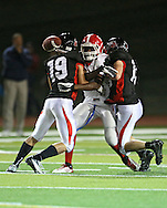 Washington's Maliek Ketchens (5) can't pull in a pass as he is hit by Linn-Mar's Mason Renner (19) and Austin Burbridge (15) during the second quarter of the game between Cedar Rapids Washington and Linn-Mar at Linn-Mar Stadium in Marion on Friday, September 14, 2012.
