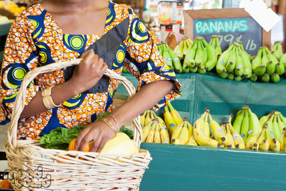 Midsection of African American in traditional wear with vegetable basket at super market