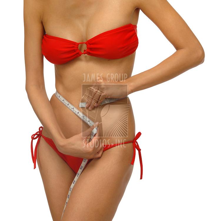 Slim woman measuring waistline with a measuring tape