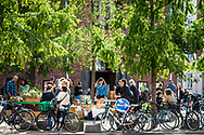 A busy outdoor cafe scene with bicycles in the foreground at Vesterbro in Copenhagen.