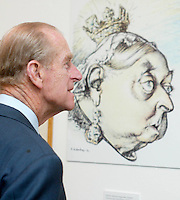 Prince Philip, the Duke of Edinburgh looks at a cartoon of Queen Victoria from 1879 by C Leandre from Le Rire magazine, France during a visit to a Cartoon Art exhibition at the Mall Gelleries in London on December 4, 2002.   (Photo by Anwar Hussein)