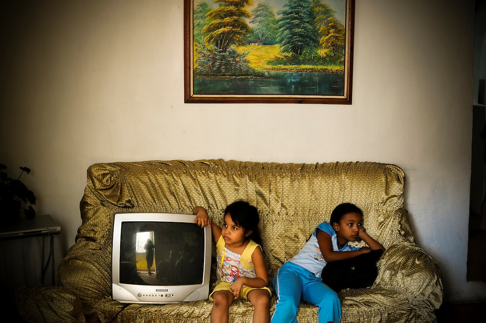 "Maria Gabriela Cabeza Pompa, 5, (left) and her cousin, Andrea Acosta, 9, (right) sit with their damaged television set in the Jose Felix Ribas slum in Petare, a large group of slums in Caracas, Venezuela. ""Now I can't watch cartoons"" sighs Maria Gabriela. The T.V. was damaged by electrical shorts, a common complaint among Petare residents since the government initiated electricity rationing; cutting off power for several hours, several times a week."