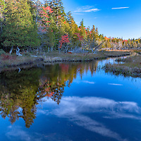 Clouds and bright blue sky reflect in the calm surface of Jordan Pond. In Acadia National Park, Bar Harbor, Maine.