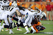 The Los Angeles Chargers defense strips the ball and causes a fourth quarter fumble (recovered by the Chargers) on a run by Denver Broncos running back Jamaal Charles (28) makes a cut as he runs the ball during the 2017 NFL week 1 regular season football game against the Los Angeles Chargers, Monday, Sept. 11, 2017 in Denver. The Broncos won the game 24-21. (©Paul Anthony Spinelli)