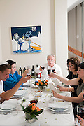 family sitting around a table set for a Jewish Festive meal on Passover (transliterated as Pesach or Pesah)