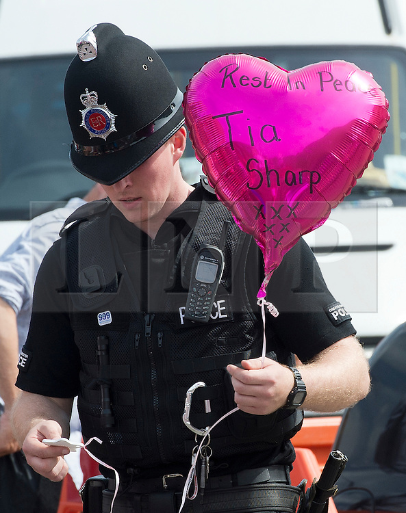 © Licensed to London News Pictures. 11/08/2012 . A police officer holding a balloon with the words 'Rest In Peace, Tia Sharp' written on it, given by a member of the pubic, on The Lindens New Addington where a body was discovered in the hunt for missing 12 year-old schoolgirl Tia Sharp. Photo credit : LNP