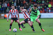 Forest Green Rovers James Jennings and Cheltenham Town's Jack Barthram battle foe the ball during the Vanarama National League match between Cheltenham Town and Forest Green Rovers at Whaddon Road, Cheltenham, England on 21 November 2015. Photo by Shane Healey.