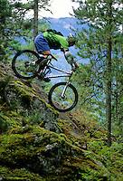 A male rider mountain bikes a steep mossy granite rock on Cut Yer Bars trail, Whistler BC Canada.