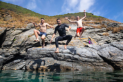 © Licensed to London News Pictures. 04/08/2018. St Austell, UK. Charlie Nicholson (left), Olly Nicholson (centre) and Sam Crofts (right) jump into the sea off the coast path near Gorran Haven, Cornwall during hot weather. Photo credit : Tom Nicholson/LNP