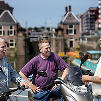 Nederland, Zaandam , 5 juli 2013.<br /> Wandeling door de binnenstad van Zaandam. Starten bij De Werf aan de Oostzijde. Daarvandaan kun je lopen op een soort boulevard tussen de flats en het water. De eerste stop is De Fabriek, filmhuis en eetcafé met terras aan de Zaan met uitzicht op de sluis. Daarna de sluis zelf.<br /> Dan langs het winkelgebied richting de Koekfabriek: Het oude Verkade pand dat is verbouwd en waar nu de bieb en sportschool en restaurant etc. in zitten.<br /> (Dat is aan de overkant van het startpunt) en misschien nog de Zwaardemaker meepakken aan de Oostzijde. Dat is een oud pakhuis die Rochdale enige jaren geleden heeft verbouwt tot appartementen met een stukje Nieuwbouw.<br /> Ook doen: het Russische buurtje vlakbij de Zaan. Dit jaar staat Rusland in de schijnwerpers en Zaandam heeft een speciale band met Rusland, vanwege het Czaar Peterhuisje en de Russische buurt. <br /> Op de foto:Sluis met sluiswachters en accijnshuisje.<br /> Foto:Jean-Pierre Jans<br /> Starten bij De Werf aan de Oostzijde. Daarvandaan kun je lopen op een soort boulevard tussen de flats en het water. De eerste stop is De Fabriek, filmhuis en eetcafé met terras aan de Zaan met uitzicht op de sluis. Daarna de sluis zelf.<br /> Dan langs het winkelgebied richting de Koekfabriek: Het oude Verkade pand dat is verbouwd en waar nu de bieb en sportschool en restaurant etc. in zitten.<br /> (Dat is aan de overkant van het startpunt) en misschien nog de Zwaardemaker meepakken aan de Oostzijde. Dat is een oud pakhuis die Rochdale enige jaren geleden heeft verbouwt tot appartementen met een stukje Nieuwbouw.<br /> Ook doen: het Russische buurtje vlakbij de Zaan. Dit jaar staat Rusland in de schijnwerpers en Zaandam heeft een speciale band met Rusland, vanwege het Czaar Peterhuisje en de Russische buurt. <br /> Op de foto: Zaandamse mannen met elkaar in gesprek. Op de achtergrond de sluis met sluiswachters en accijnshuisje.<br /> Foto:Jean-Pierre Jans