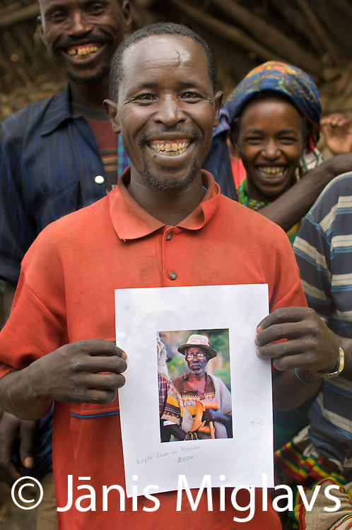 Kunina holds a photo of his deceased father Kuyta Lamita, I took in 2001, in Busso village, Konso tribe, Ethiopia.