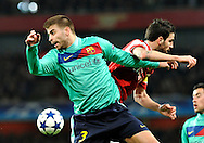 Arsenal midfielder Cesc Fabregas, challenges for the ball with Barcelona defender Gerard Pique during a Champions League, round of 16 first leg soccer match between Arsenal and Barcelona at the Emirates stadium in London, UK, Wednesday, Feb. 16, 2011.
